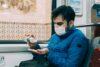 Rapaz de casaco azul e máscara passa álcool em gel nas mãos enquanto está sentado em veículo coletivo